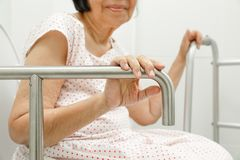 Elderly woman holding on handrail in toilet. Elderly woman holding on handrail in toilet at home stock image