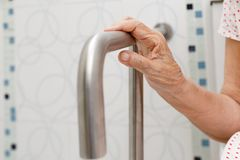 Elderly woman holding on handrail in toilet. Elderly woman holding on handrail in toilet at home royalty free stock photography