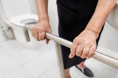 Elderly woman holding on handrail in toilet. Elderly woman holding on handrail in toilet room stock photos