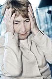 Elderly woman holding head Stock Images