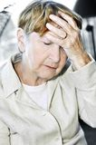 Elderly woman holding head Stock Photography