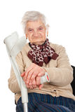 Elderly woman holding her crutch Stock Images
