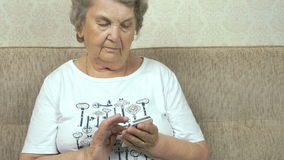 Elderly woman holding a mobile phone at home stock video