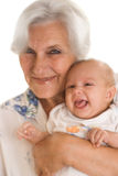 Elderly woman holding a newborn Stock Photography