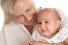 Elderly woman holding a newborn Stock Image