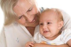Elderly woman holding a newborn Stock Image