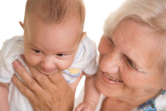 Elderly woman holding a newborn Royalty Free Stock Image