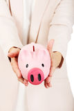 Elderly woman holding piggy bank Royalty Free Stock Image