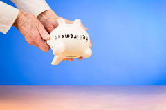 Elderly woman holding piggybank upside down Stock Images