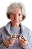 Elderly woman holding pill. Old woman holding a filled pill dispenser Stock Image