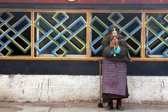 Elderly woman holding prayer wheel. An elderly woman holding prayer wheel lying on old wall.Photo taken in tibet on Aug. 2,2009 Royalty Free Stock Photo