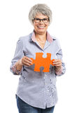 Elderly woman holding a puzzle piece Royalty Free Stock Images