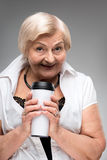 Elderly woman holding thermos cup Stock Photo