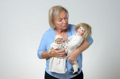 Elderly woman holding two antique dolls Royalty Free Stock Images