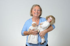 Elderly woman holding two antique dolls. In her arms with a smile, conceptual of a collector or of a woman reminiscing her childhood, over grey stock photos