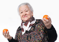 Elderly woman holding two tangerines i. N her hand against white background stock photo