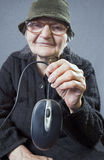 Elderly woman holding up a computer mouse Royalty Free Stock Image