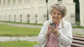 Elderly woman holds silver smart phone outdoors stock footage