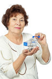 Elderly woman holds toy shopping cart Royalty Free Stock Photo