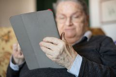 Elderly woman using tablet e-book. Elderly woman at home sitting on the sofa using tablet e-book portrait selective focus on hands Stock Photography