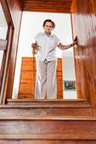Elderly woman at home using a cane to get down the stairs royalty free stock image
