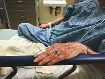 Elderly woman in hospital bed as a patient. Elder woman is hospitalized, wearing a blue gown, and resting her hand on a handrail.  She wears a pulse oximeter on Stock Photos