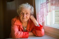 Elderly woman in the house near the window. Stock Photos