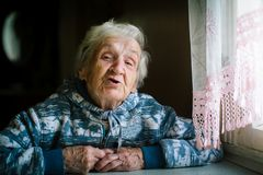 Elderly woman in the house at the table. Portrait of elderly woman in the house at the table stock photos