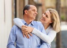 Elderly woman hugging man while walking Stock Image