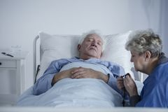 Elderly woman and ill husband Stock Image