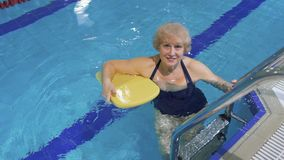 Elderly woman invites to swim in the pool. Elderly woman swims in the swimming pool. Senior woman has a healthy lifestyle and spend her leisure time swimming in stock footage
