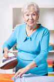 Elderly woman ironing shirt Stock Photos