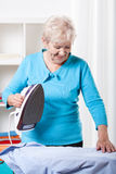 Elderly woman ironing. Smiling elderly woman ironing blue shirt at home stock images