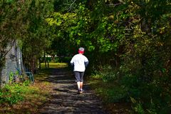 Elderly Woman Jogging Through A Path In A Park stock photography