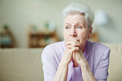 Elderly woman. Keeping hands by her lips Stock Photo