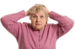 The elderly woman keeps for a head Stock Photos