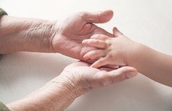 Elderly woman and a kid hands together royalty free stock photos