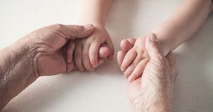 Elderly woman and a kid hands together royalty free stock photography