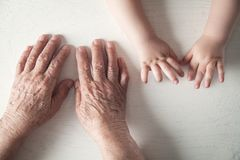 Elderly woman and a kid hands together stock photography
