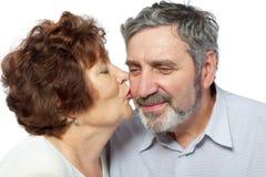 Elderly woman kisses husband Stock Photo