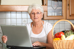 Elderly woman in kitchen Royalty Free Stock Photography