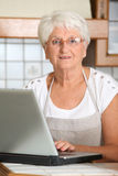 Elderly woman in kitchen Royalty Free Stock Photo