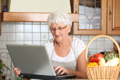 Elderly woman in kitchen looking for recipe Stock Image