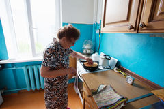 Elderly woman on the kitchen Royalty Free Stock Image