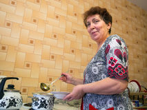 Elderly woman in the kitchen pouring soup into a bowl Stock Photos
