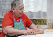 Elderly woman kneading dough Royalty Free Stock Photography