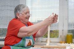 Elderly woman kneading dough stock image