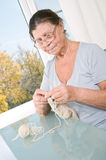 An elderly woman knits. An elderly woman knit woolen socks. Studio photography Royalty Free Stock Photography