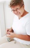 Elderly woman knitting stock images