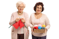 Elderly woman knitting with another elderly woman helping her. Elderly women knitting with another elderly women helping her isolated on white background Royalty Free Stock Photography